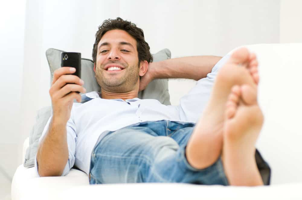 Man relaxing on sofa surfing his mobile smart phone