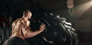 Muscular man flipping tire