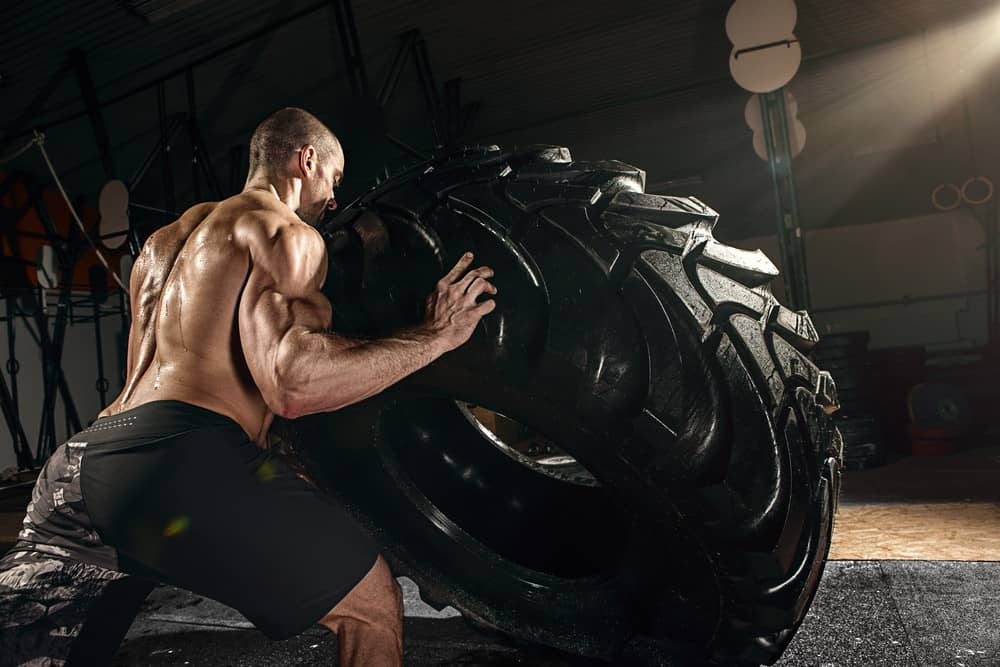Muscular man flipping tire