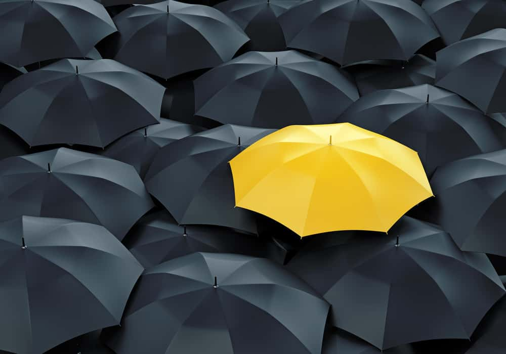 Uniuqe yellow umbrella in sea of black umbrellas