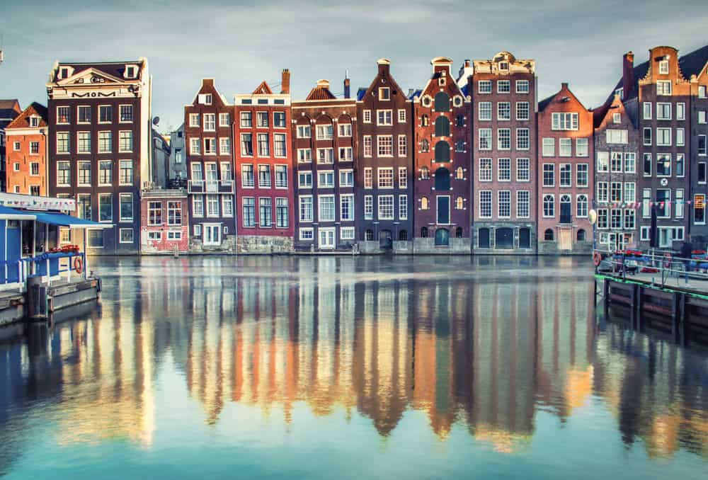Houses lining Damrak canal in Amsterdam, Netherlands