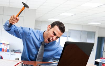 Man smashing computer with hammer