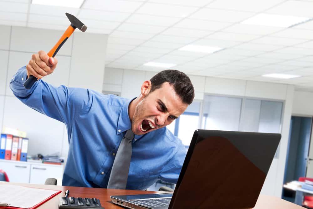 Man smashing computer with hammer