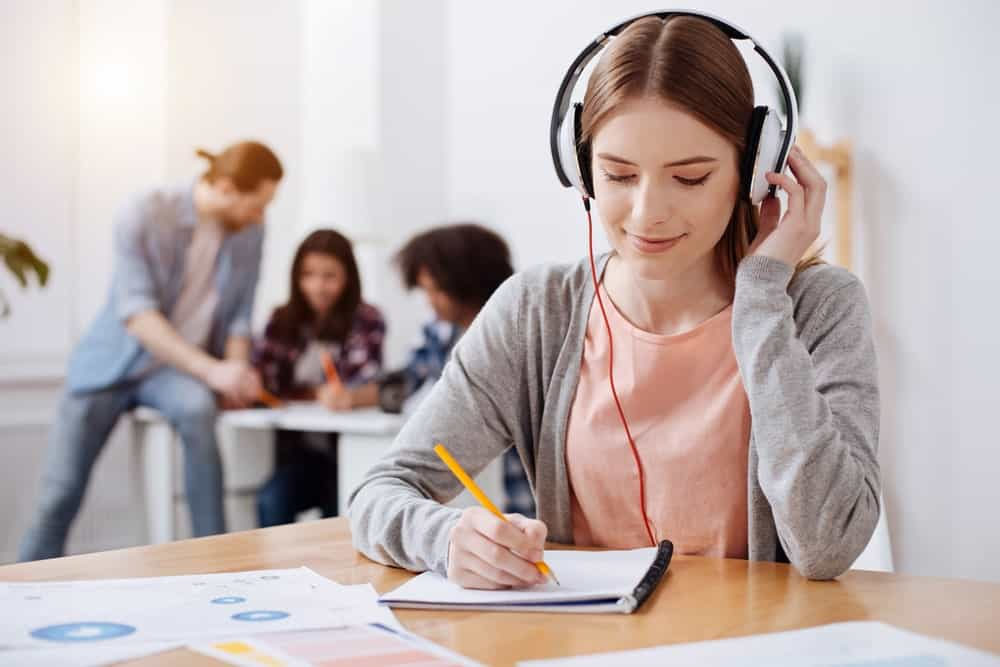 Young woman wearing a headphone while writing on a notebook.