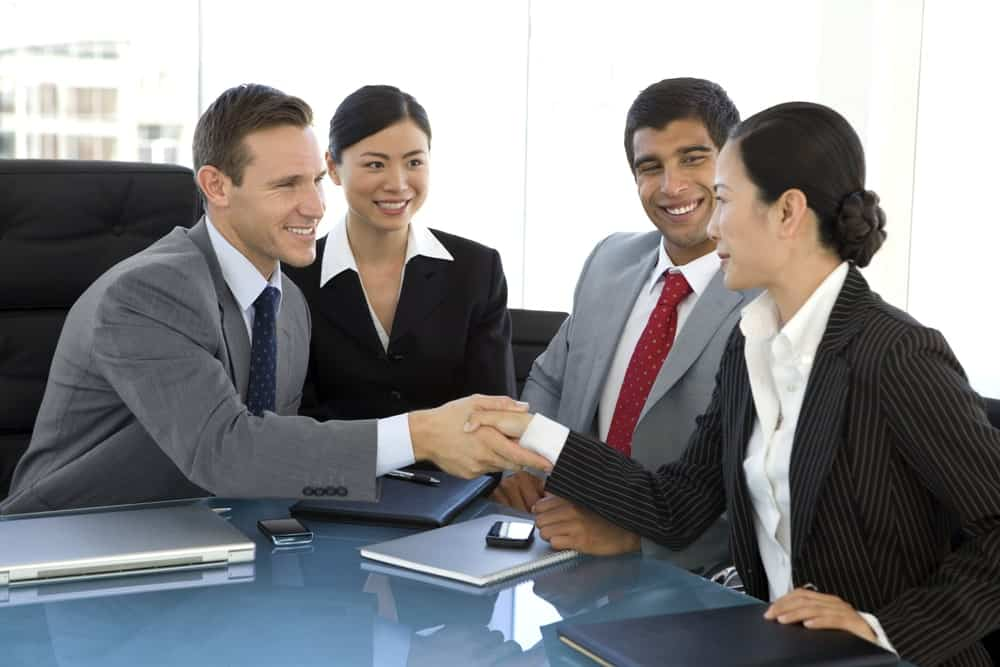 Businessman and woman shaking hands with another pair of woman and man in suit between them.