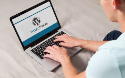 A man using WordPress on his laptop.