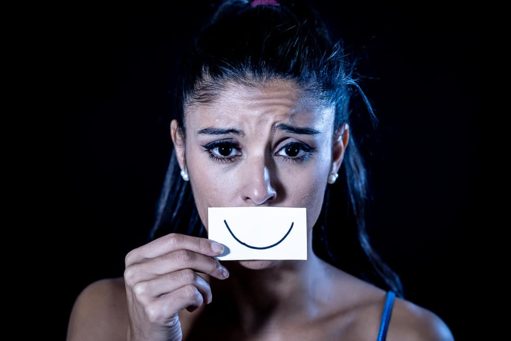 Sad woman with fake smile