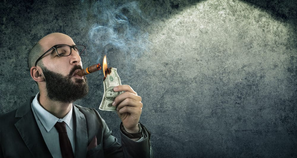 man lighting cigar with burning money
