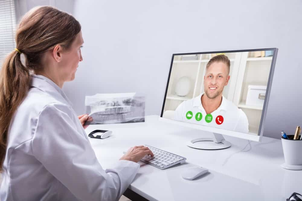 Dentist video conferencing with a man.