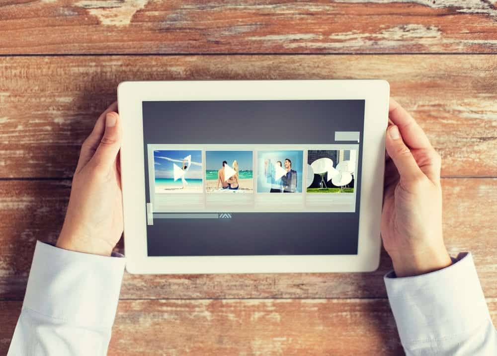 Hands holding a tablet with video gallery slideshow