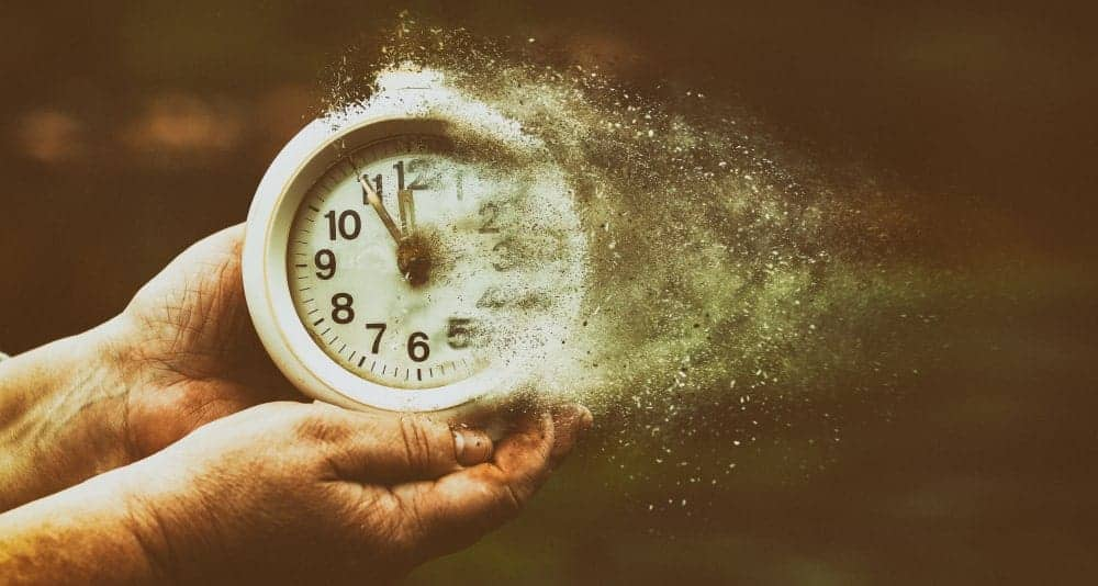 Metaphor for time as it flies by illustrated with hands holding a clock that's turning into dust.