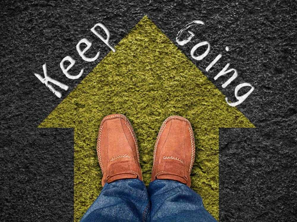 """Feet on the yellow arrow with words """"keep going""""."""