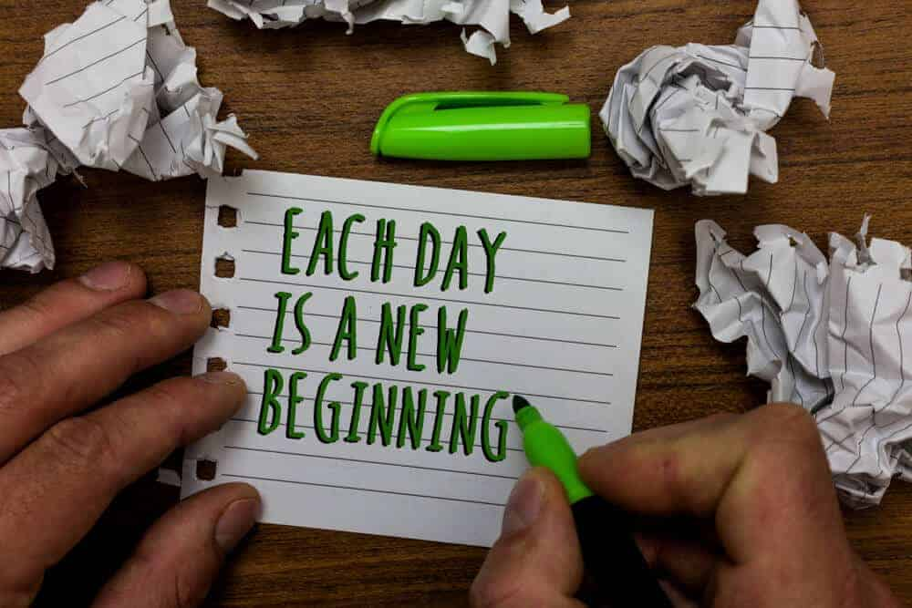 """The quote """"Each day is a new beginning"""" written on a piece of paper using a green marker."""