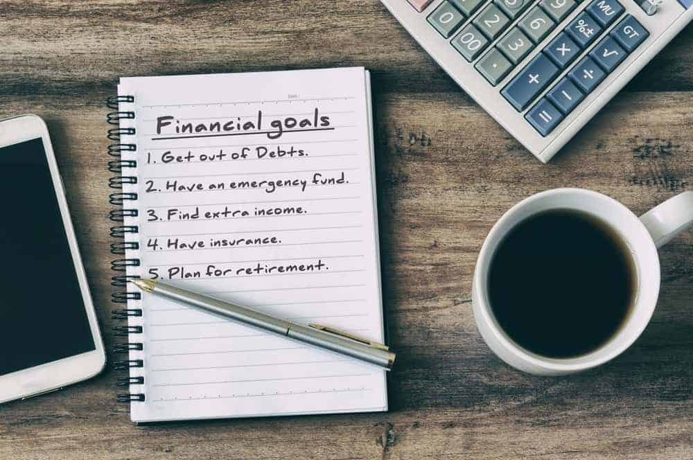 A smartphone, calculator, and a cup of coffee surrounds a notebook with a list of financial goals written on it.