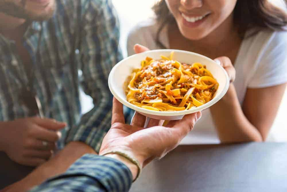 A woman fetching the man's plate of pasta.