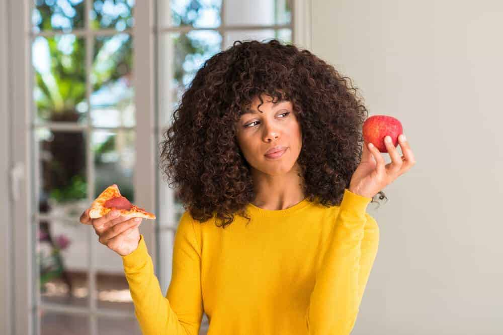 A woman wondering if she will choose the pizza or the apple.
