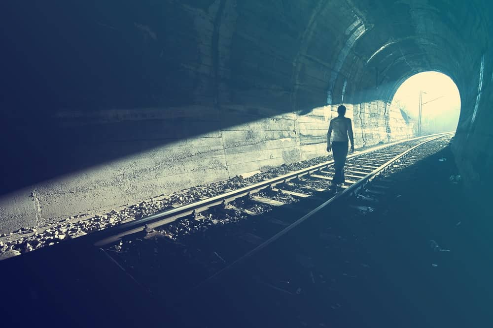 A person walking towards the light at the end of the tunnel.