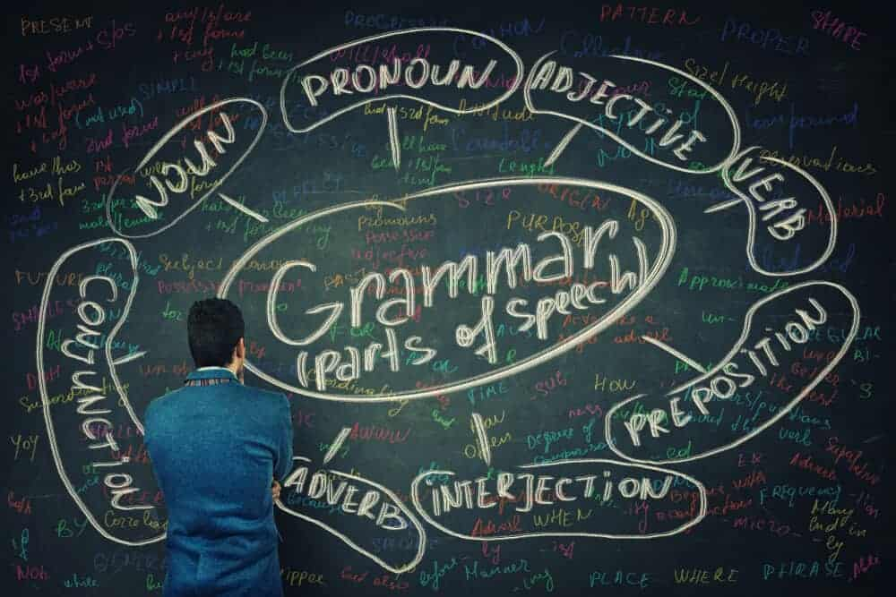 A man analyzing the parts of speech written on the blackboard.