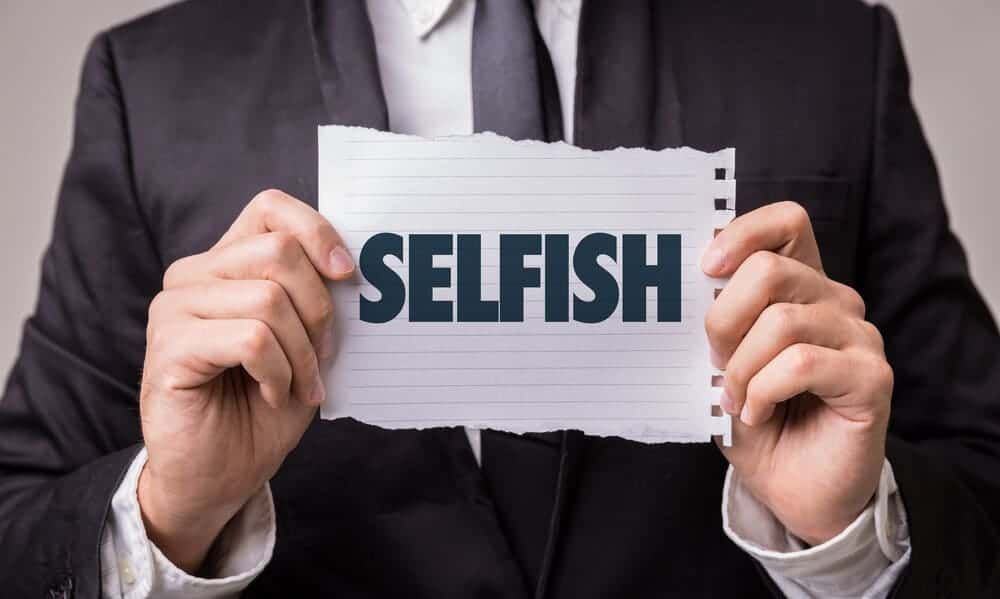 """A man in a corporate attire holding a piece of paper with the word """"selfish"""" in it."""