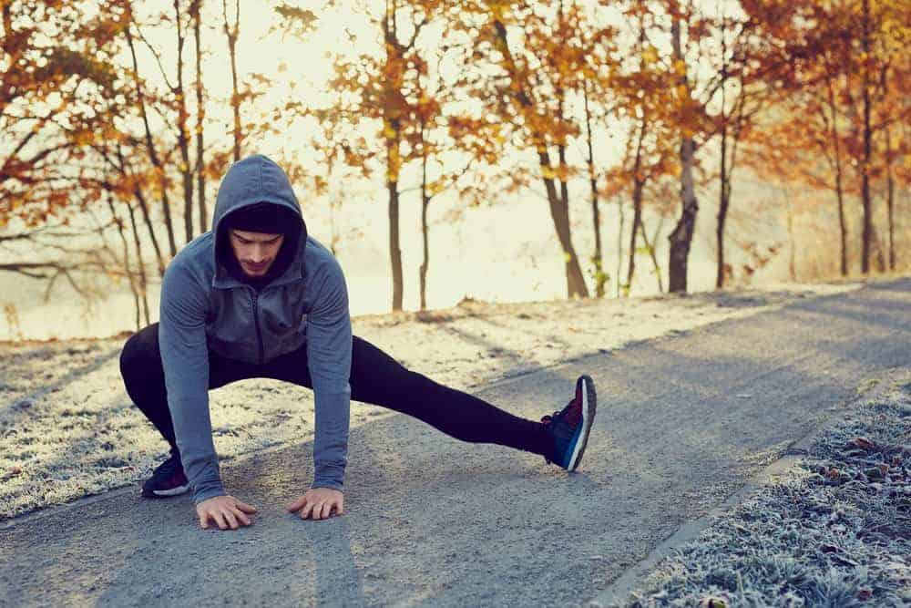 A man wearing a hoodie jacket doing a stretching outdoors.