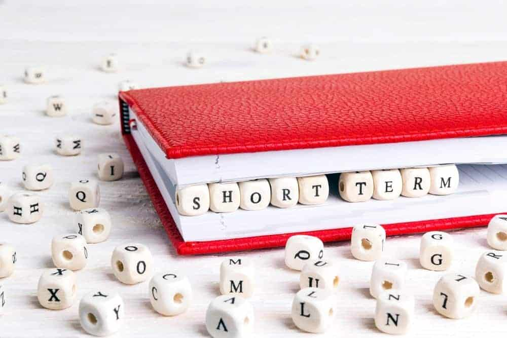 "The words ""Short Term"" spelled out in scrabble dices between pages of a red notebook."