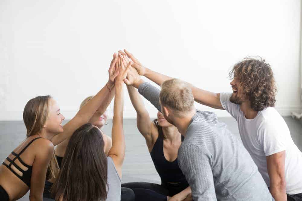 A group of friends doing a high five as a sign of teamwork.
