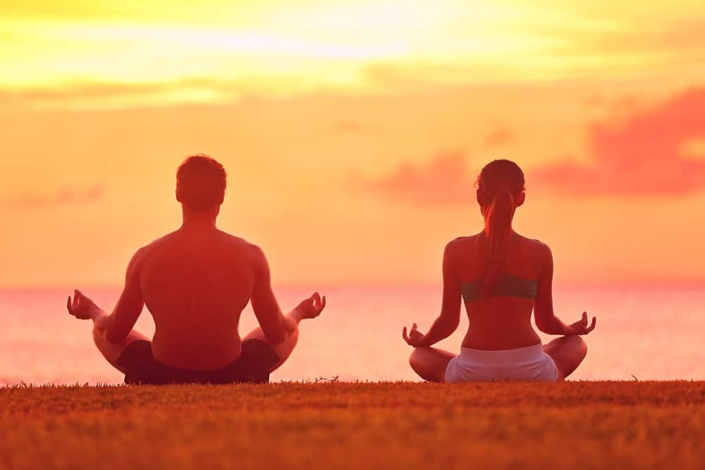 Back view of a man and a woman doing a meditation pose on the ground facing the sunset sky.