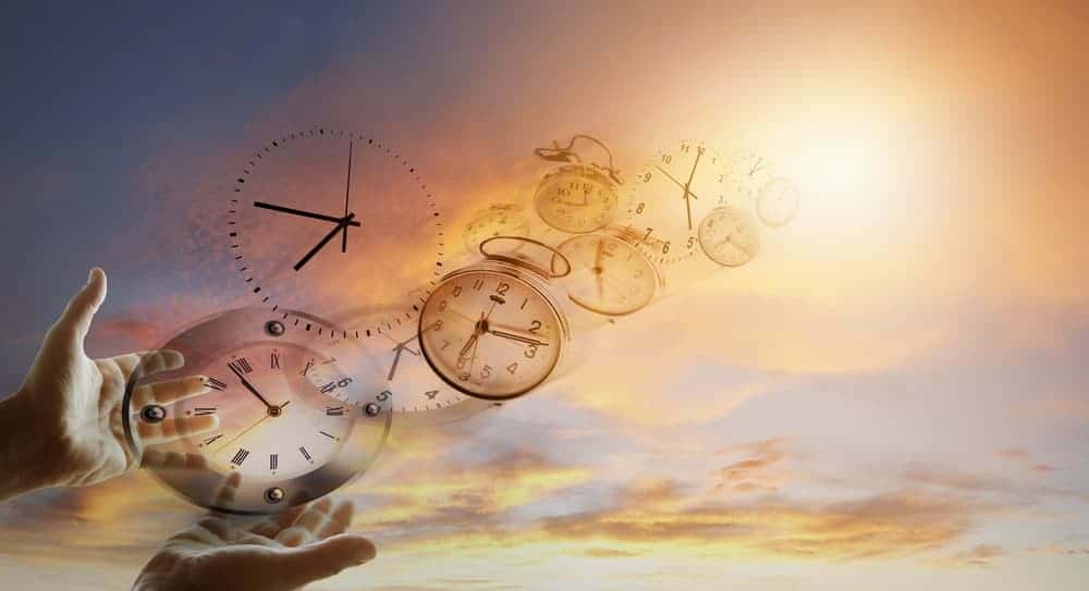 Time flies by represented by hands holding clocks that are flying towards the sky.