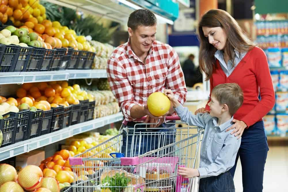 A family in supermarket shopping for fruits.