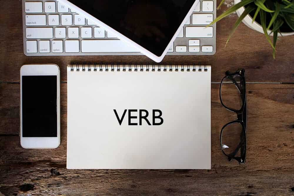 """The word """"verb"""" written on a notebook over a table together with a laptop, a phone and a pair of eyeglasses."""