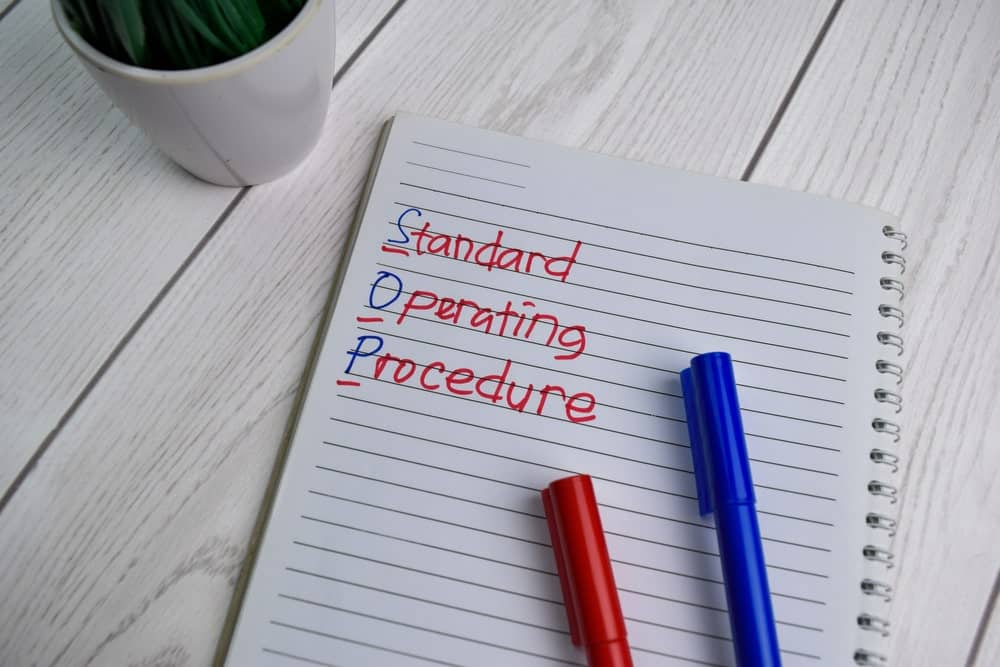 Standard Operating Procedure written on a notebook over a wood plank table.