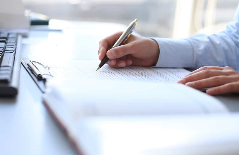 Businessman writing on a filing notebook.