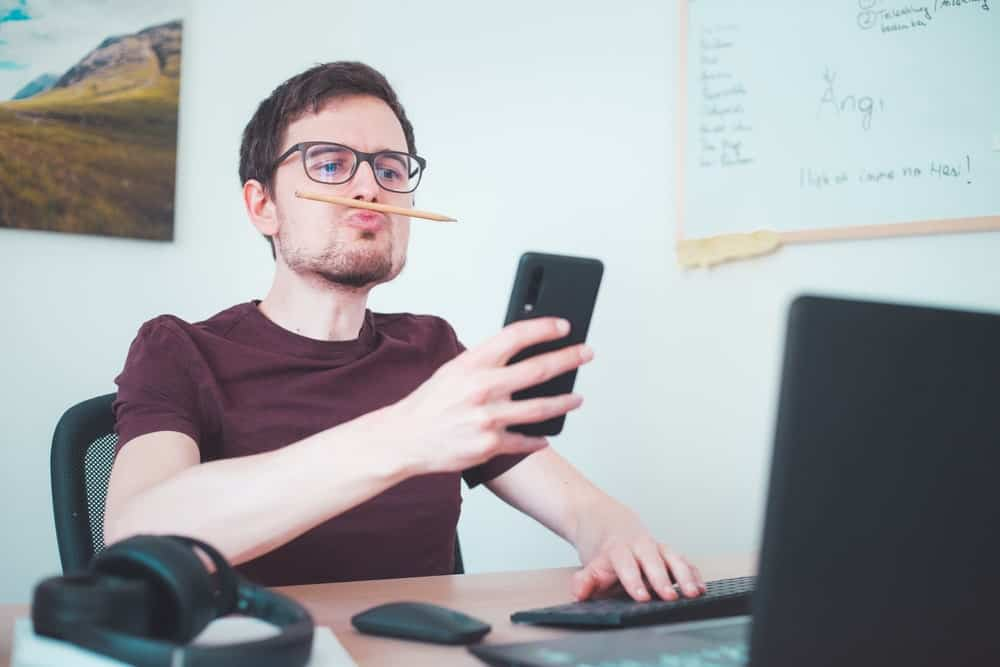Bored freelancer fools around with his pencil and looks at his smartphone.