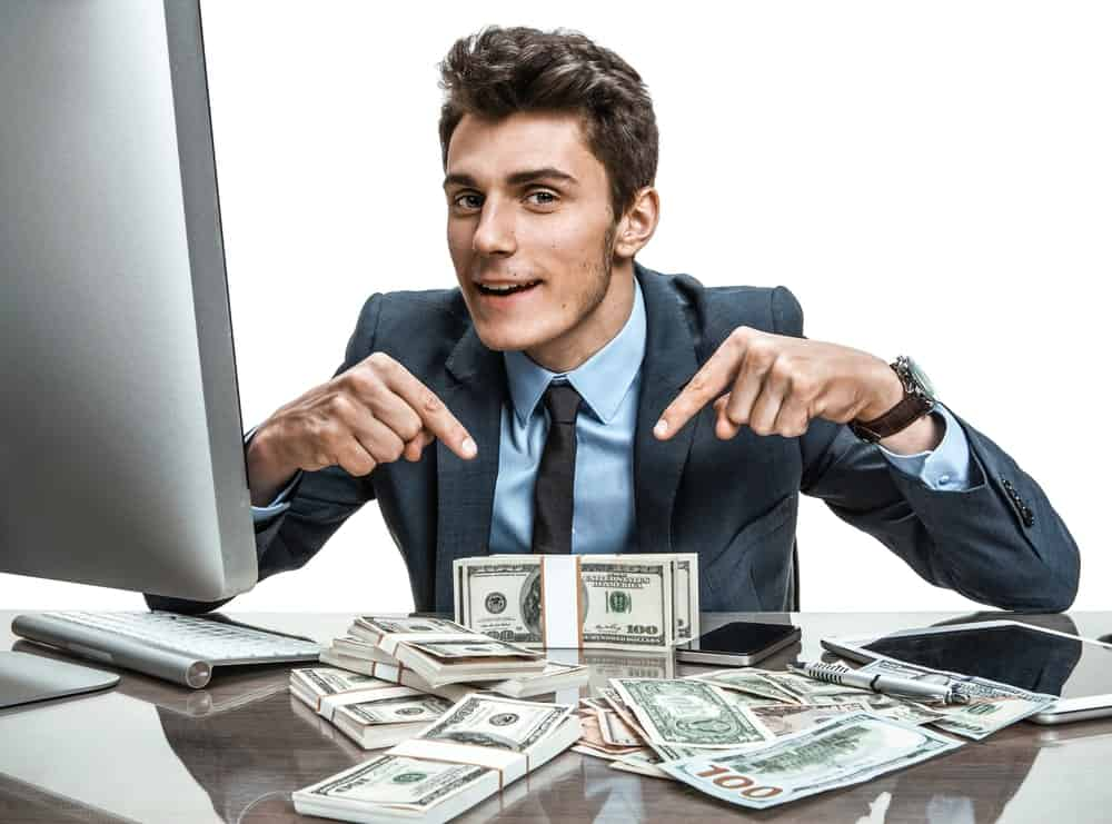 Businessman happily points at the wads of cash in front of a computer.