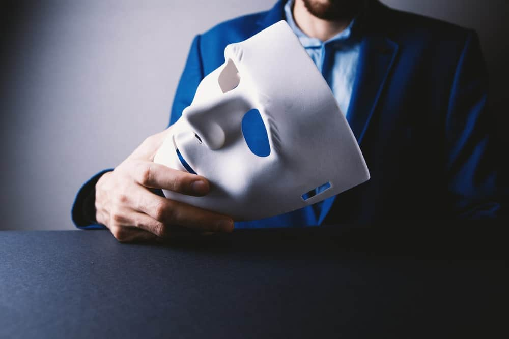 Man holds a white mask.