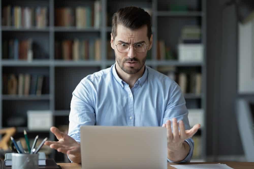 Man looks bewildered at something on his laptop screen.