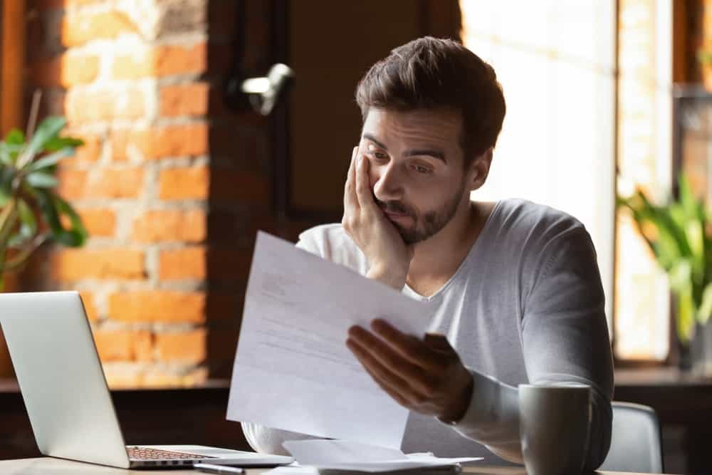 Young man looks dejectedly at a letter while sitting in front of his open laptop.
