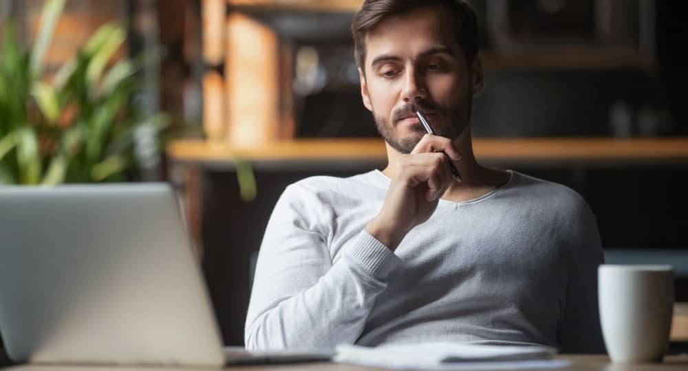 Freelancer looks pensive while holding a pen and staring at the laptop screen.
