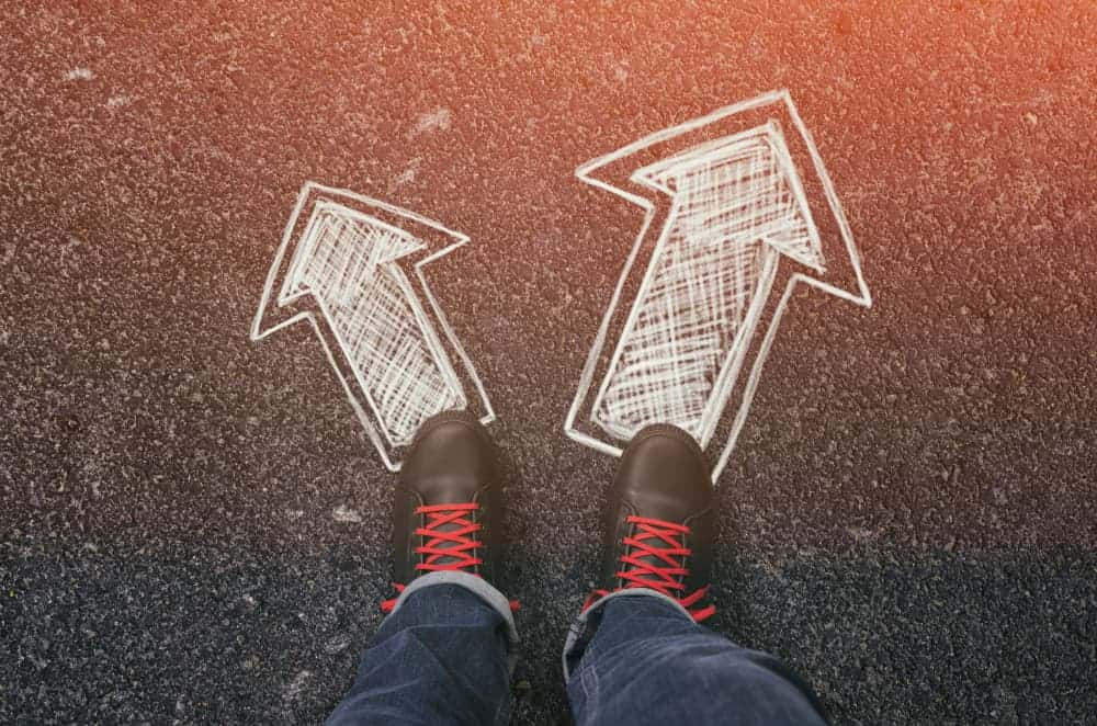 Sneakers standing on two drawn arrows  on an asphalt road pointing to different directions.