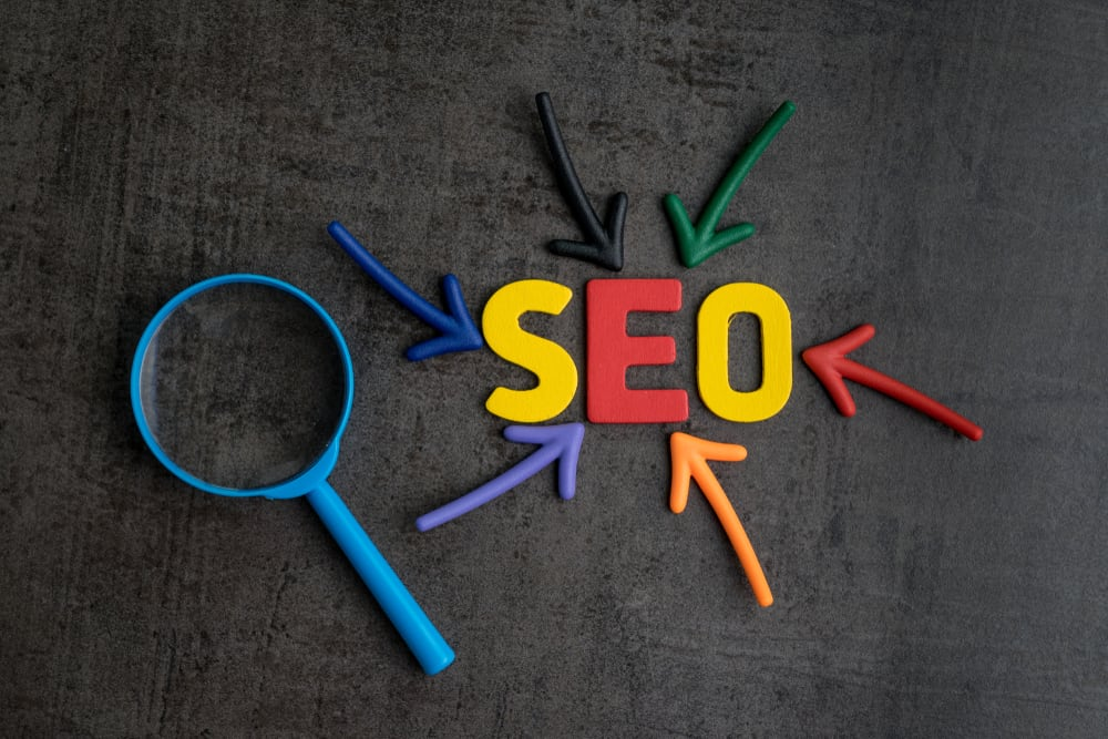Multi-colored SEO letters surrounded by multi-colored arrows pointing toward it and a blue magnifying glass.