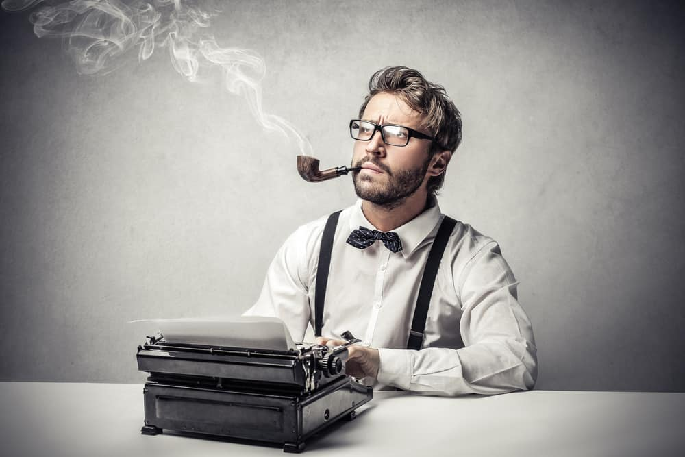 Writer with a tobacco pauses to think with hands on a typewriter.