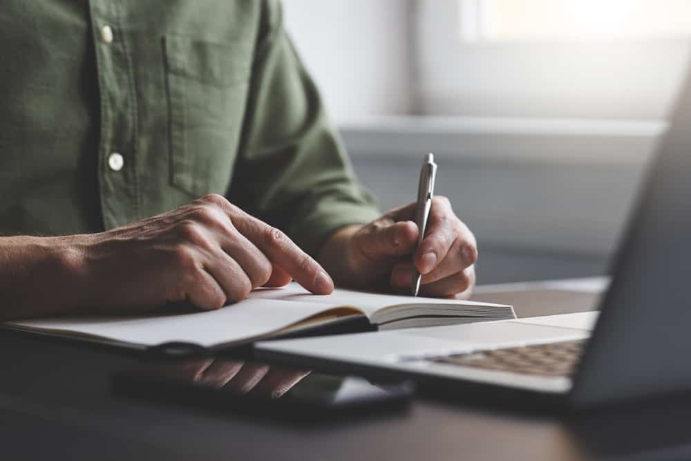 Cropped photo of a man writing on a notepad in front of an open laptop.