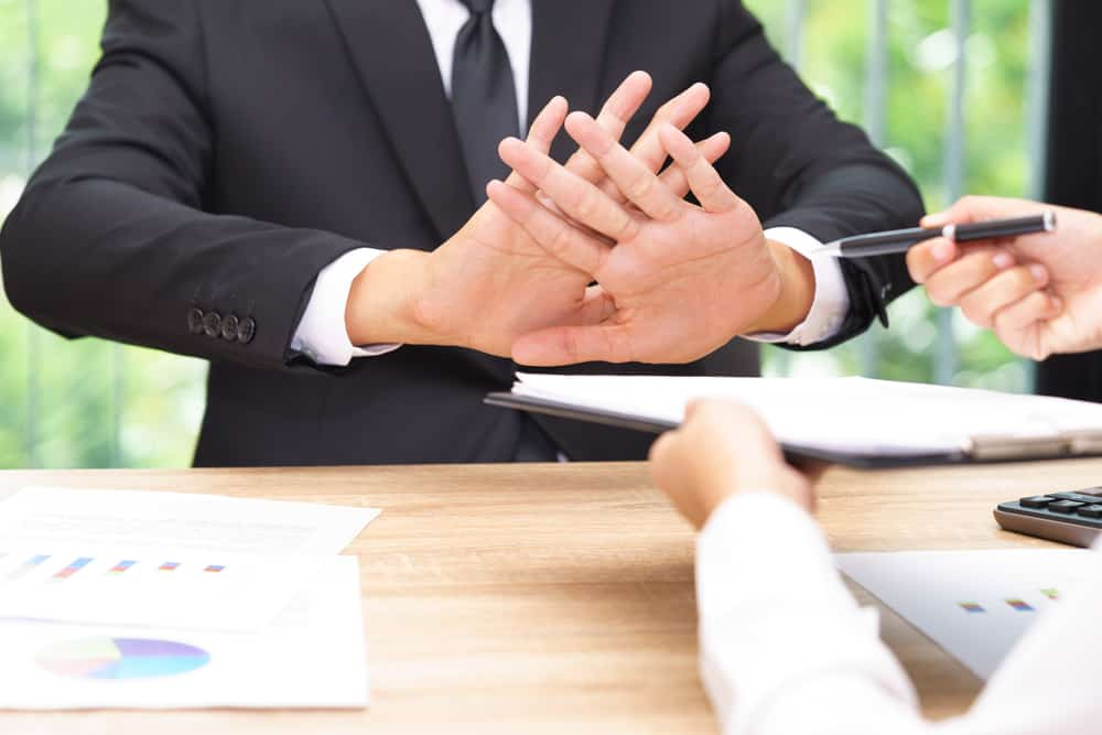 A businessman puts up his hands to refuse signing a paper contract.