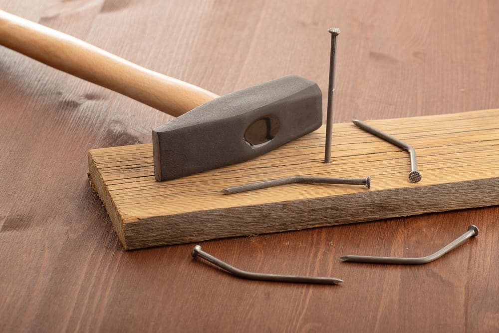 A hammer rests on a block of wood with a nail stuck out surrounded by bent nails.