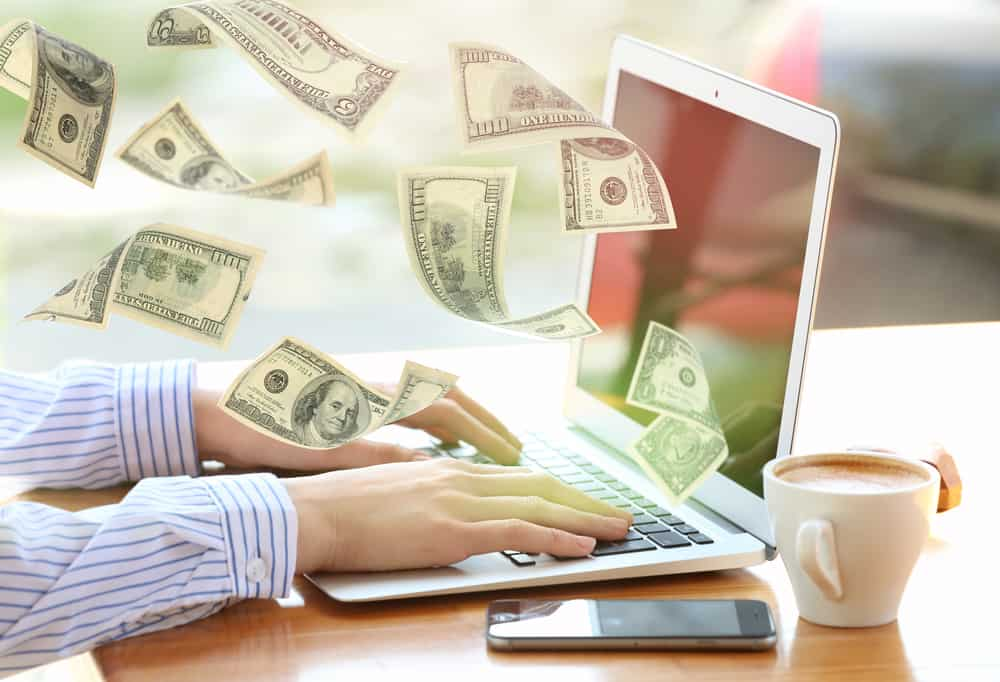 Money flying out of an open laptop while a person works.