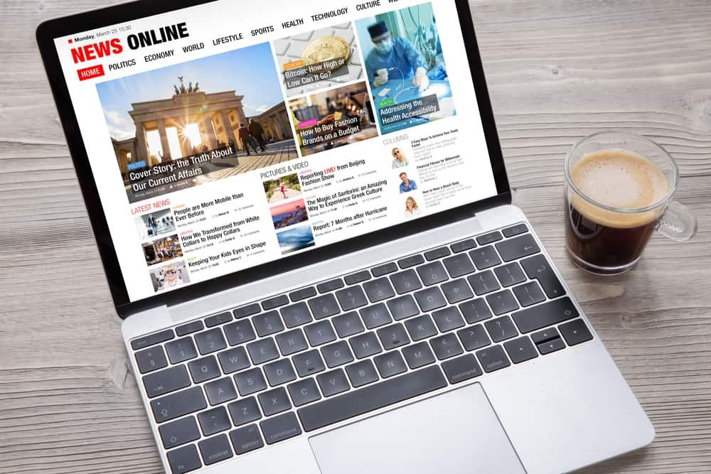 An open laptop beside a cup of coffee shows a news website.